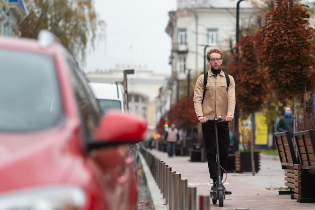 Homme occasionnel monté sur un scooter électrique