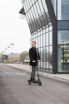 Homme occasionnel posant avec un scooter électrique