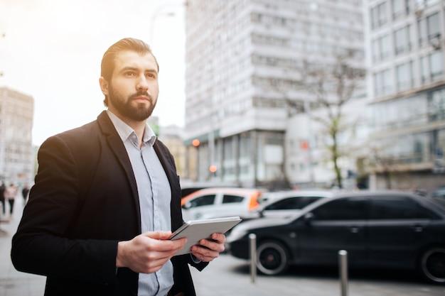 Un homme occupé est pressé, il n'a pas le temps, il va utiliser le tablet pc en déplacement. homme d'affaires faisant plusieurs tâches. homme d'affaires multitâche.