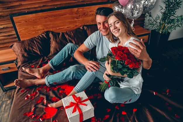 Un homme a offert un cadeau à une femme et des roses rouges. un couple est assis sur le lit avec des confettis en forme de cœur.