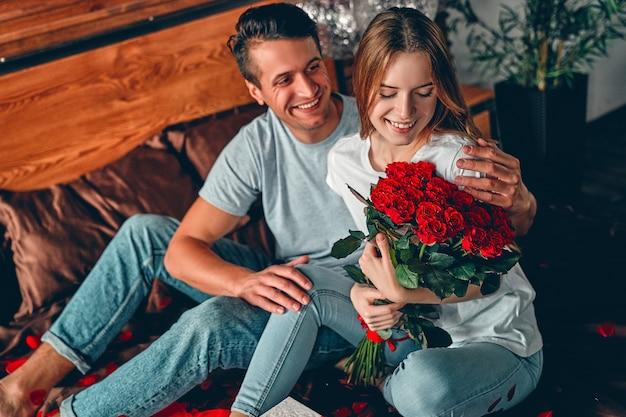 Un homme a offert à une femme des roses rouges. un couple est assis sur le lit avec des confettis en forme de cœur et des câlins.