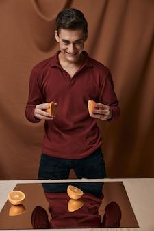 Homme avec des oranges dans ses mains chemise rouge sourire miroir sur la table. photo de haute qualité