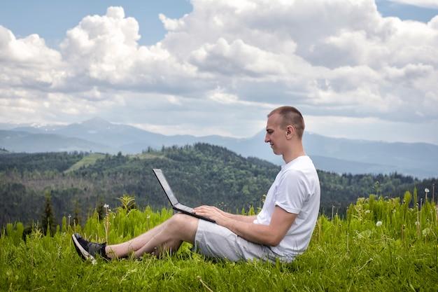 Homme avec ordinateur portable assis sur l'herbe verte sur un mur de montagnes. vue de côté
