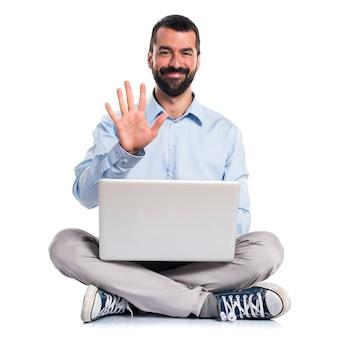 Homme avec ordinateur portable comptant cinq