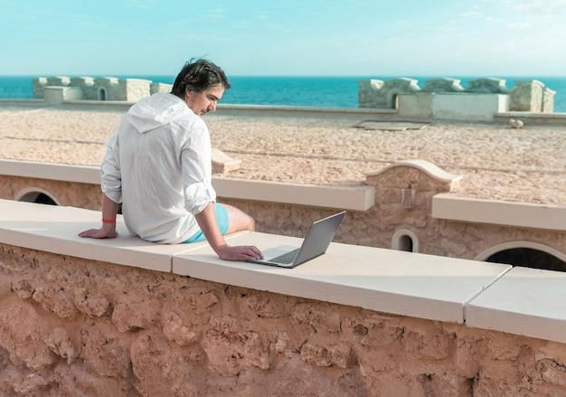 Homme avec un ordinateur portable dans ses mains au repos et travaillant comme pigiste en vacances