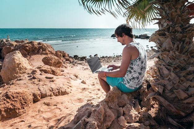 Un homme avec un ordinateur portable dans ses mains se repose et travaille comme pigiste sur la plage