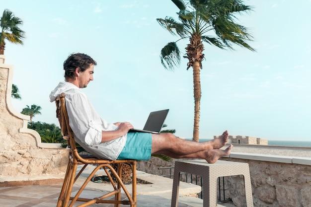 Un homme avec un ordinateur portable dans ses mains se repose et travaille comme pigiste sur la table des palmiers