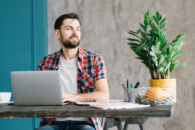 Homme avec ordinateur portable en détournant les yeux