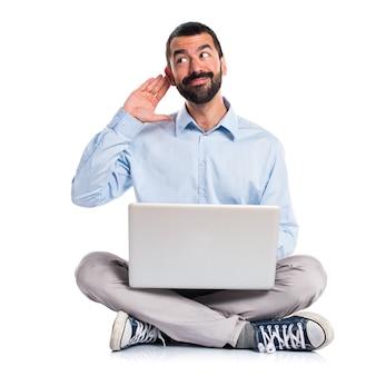 Homme avec un ordinateur portable écoutant quelque chose