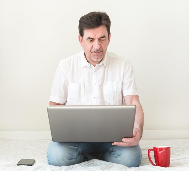 Homme avec ordinateur portable sur le lit dans la chambre. travail à domicile