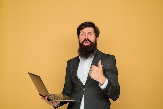 Homme avec ordinateur portable montre le pouce vers le haut bel homme d'affaires travaillant avec des affaires de bureau pour ordinateur portable