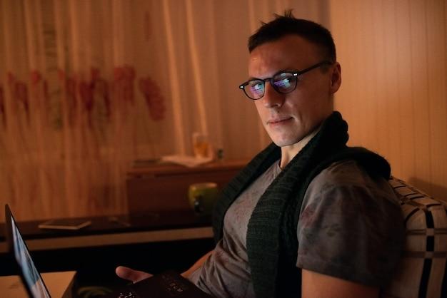Homme à l'ordinateur le soir pour n'importe quel but.