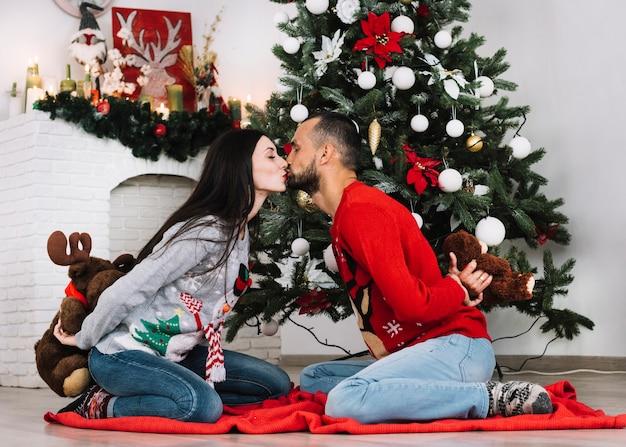 Homme avec ours en peluche embrassant femme avec duvet moelleux
