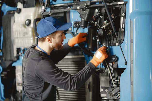 Homme avec des outils pour camion. travailleur en uniforme. camion défectueux