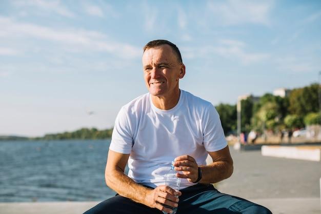 Homme ouvrant une bouteille d'eau près d'un lac