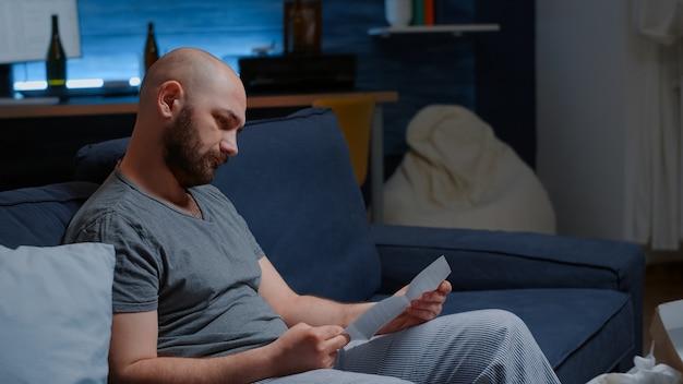 Un homme ouvre un document d'avertissement en lisant une lettre de la banque concernant le refus de prêt