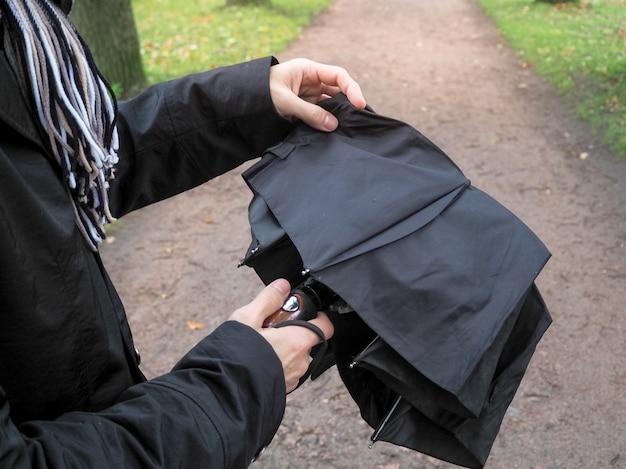 L'homme ouvre un parapluie noir