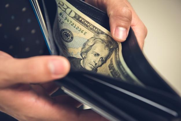 Un homme ouvre son portefeuille à la recherche d'argent