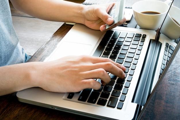 L'homme paie pour les produits en ligne en utilisant sa carte de crédit. filtre de tonalité chaud appliqué.