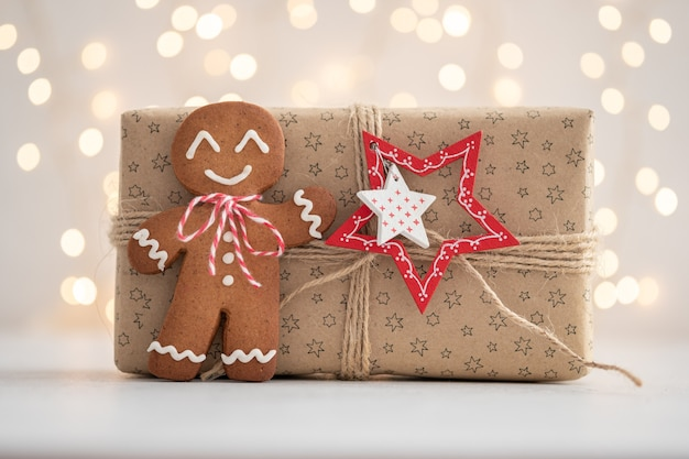 Homme de pain d'épice souriant avec cadeau et lumières