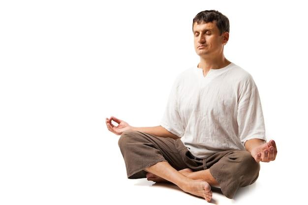 Homme paisible faisant du yoga et méditant - isolé sur fond blanc