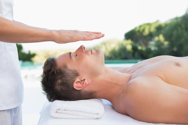Homme paisible recevant un traitement de reiki près de la piscine