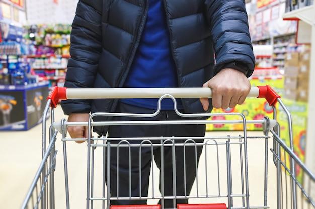 Homme avec un panier marche dans un supermarché. main et partie du panier