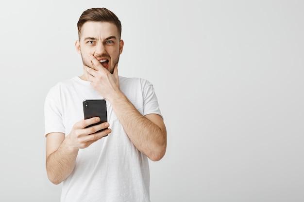 Homme en panique tenant un téléphone mobile et à la recherche après avoir fait une erreur