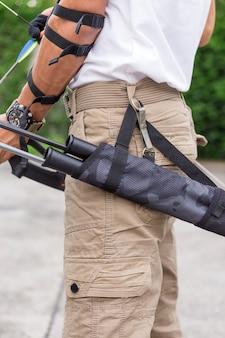 Homme en pantalon cargo avec arc et flèches