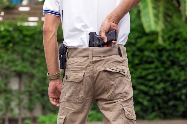 Homme en pantalon cargo avec pistolet
