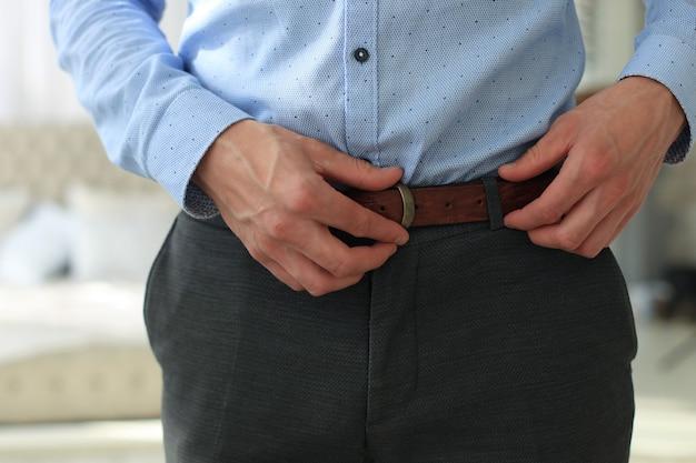 Un homme en pantalon gris et chemise bleue boutonnait une ceinture de pantalon en cuir marron.