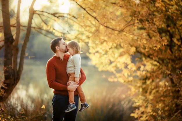 Un homme papa tient sa fille dans ses bras sur le fond d'un lac sur une promenade d'automne