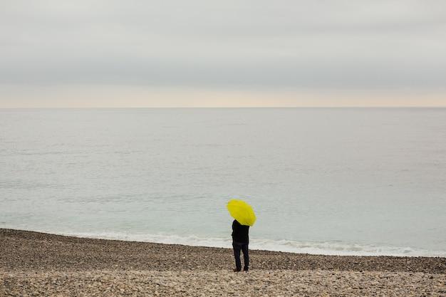 Homme avec un parapluie jaune sur la rive de la mer méditerranée