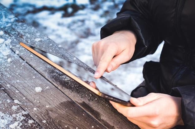 Un homme parcourt des photos sur une tablette alors qu'il est assis à une table en bois