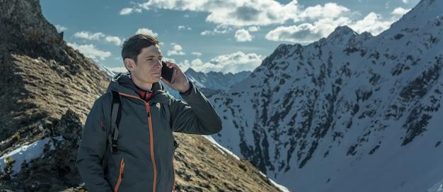 Homme parlant au téléphone au sommet d'une montagne enneigée loin de la civilisation. disponibilité de l'activité et de la communication