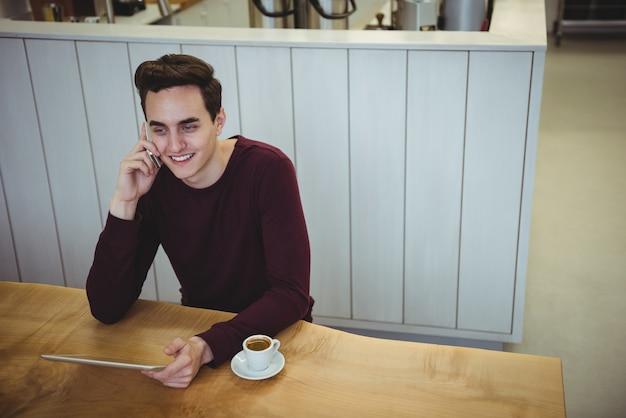 Homme parlant au téléphone mobile et tenant une tablette numérique