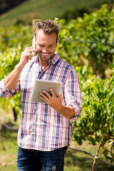 Homme parlant au téléphone tout en utilisant une tablette au vignoble