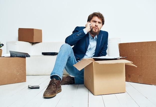 Homme parlant sur les cabines téléphoniques avec des effets personnels déménagement déballage officiel
