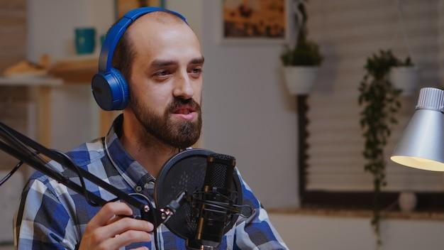 Homme parlant du succès dans son podcast en utilisant une technologie d'enregistrement professionnelle. émission créative en ligne production en direct hôte de diffusion sur internet diffusant du contenu en direct, enregistrant des médias sociaux numériques