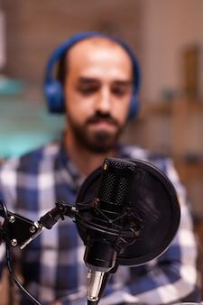 Homme parlant du succès de son podcast en utilisant la technologie d'enregistrement professionnelle en home studio. spectacle en ligne créatif hôte de diffusion internet de production en direct diffusant du contenu en direct.