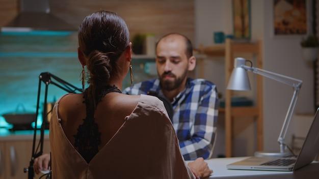 Homme parlant avec un influenceur dans un home studio portant des écouteurs et parlant au micro. spectacle en ligne créatif production en direct hôte de diffusion sur internet diffusant du contenu en direct, enregistrement de réseaux sociaux numériques