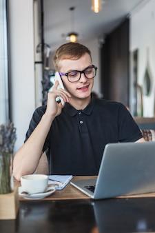Homme parlant par téléphone à la table