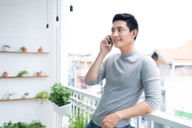 Homme parlant sur smartphone debout sur balcon à la maison.