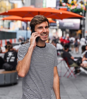 Homme parlant sur un smartphone devant une terrasse