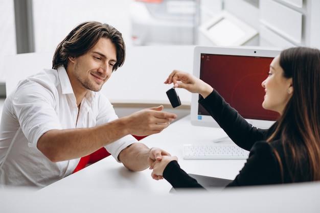 Homme parlant avec vendeuse dans une salle d'exposition