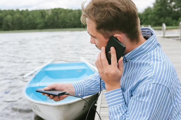 Un homme parle au téléphone avec un chargeur power bank à la main. dans le contexte de l'eau et de la rivière du lac.