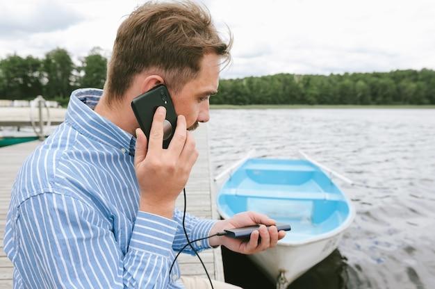 Un homme parle au téléphone avec un chargeur power bank à la main. sur fond d'eau et de bateaux.