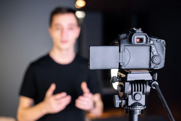 L'homme parle à la caméra, s'enregistre dans un vlog. travailler à domicile. jeune créateur de contenu