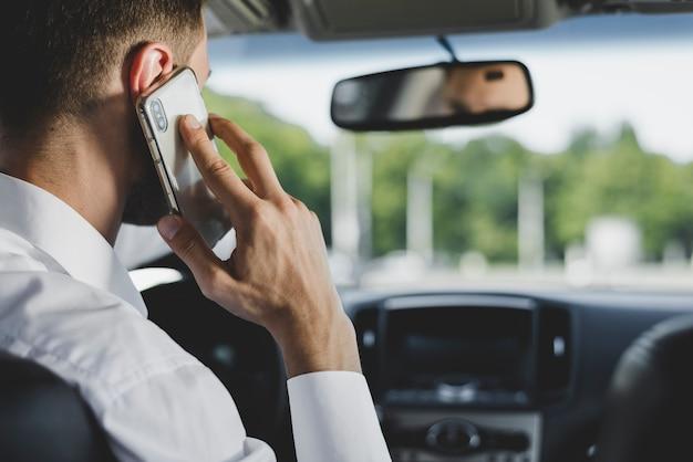 L'homme parle sur smartphone en conduisant la voiture