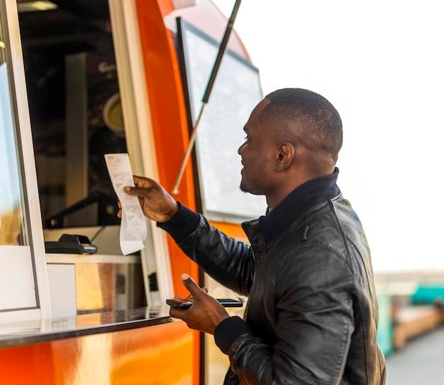 Homme passant commande au camion alimentaire